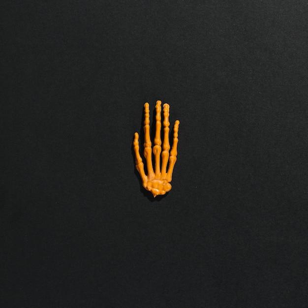 Main squelette orange au milieu Photo gratuit