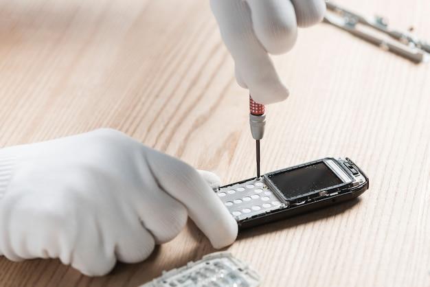 Main de technicien réparant un téléphone portable sur fond en bois Photo gratuit