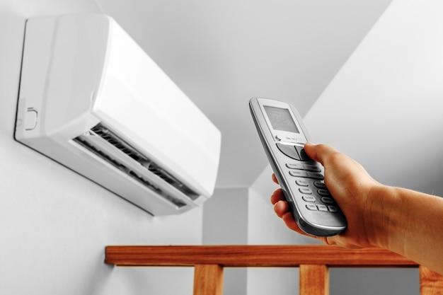 Main avec télécommande dirigée sur le climatiseur sur le mur Photo Premium