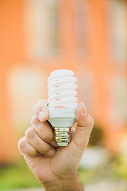 Main tenant une ampoule fluorescente compacte à économie d'énergie à l'extérieur Photo gratuit