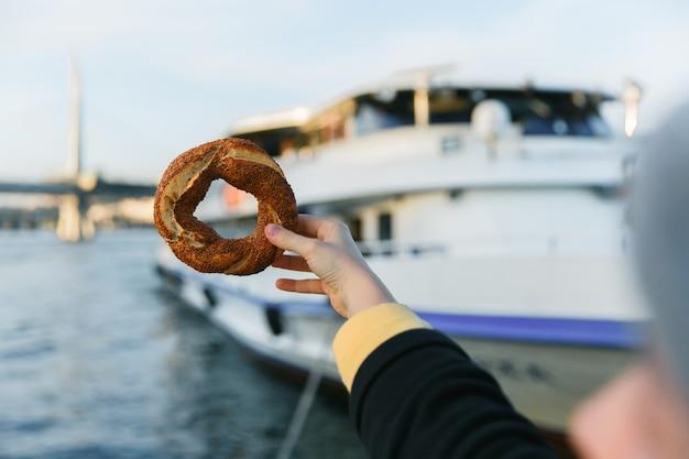 Main Tenant Un Bagel Turc Traditionnel Simit Le Fond Bleu De La Baie Du Bosphore. Photo Premium
