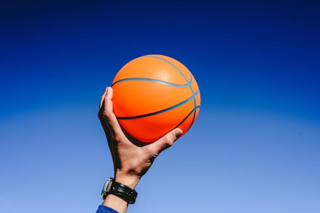 Main Tenant Un Ballon De Basket Orange Sur Fond De Ciel Bleu, Invitation à Jouer Photo Premium