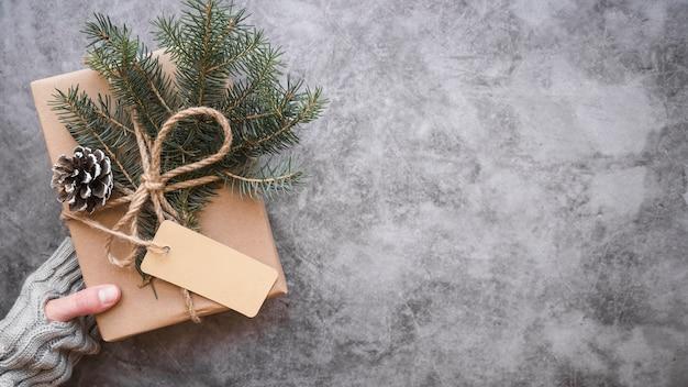 Main tenant une boîte cadeau décorée avec des branches, des étiquettes et des sapins Photo gratuit