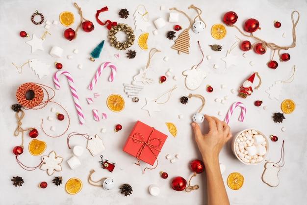 Main tenant une boîte cadeau emballée. décoration de noël avec coffrets cadeaux, corde, guimauves, biscuits au pain d'épices Photo Premium