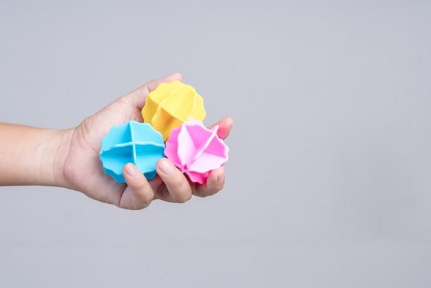 Main tenant une boule en plastique pour machine à laver Photo Premium
