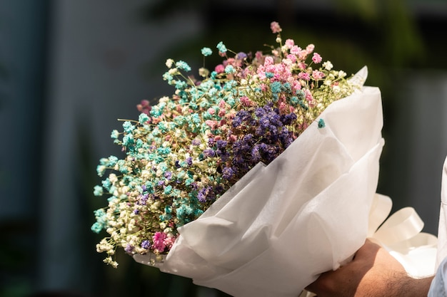 Main tenant un bouquet de fleurs de gypsophile séchées enveloppées dans du papier Photo Premium