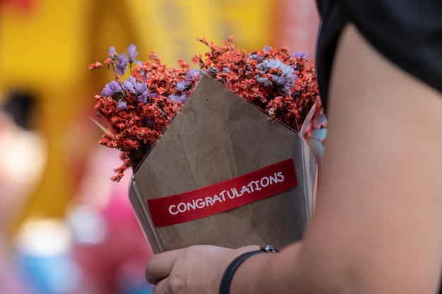 Main tenant un bouquet de fleurs d'oranger séchées enveloppées dans du papier Photo Premium
