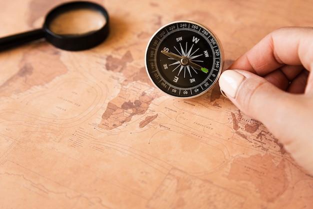 Main tenant une boussole sur une carte Photo gratuit