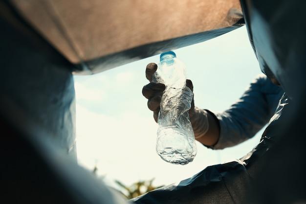 Main tenant une bouteille de déchets putt dans un sac noir Photo Premium