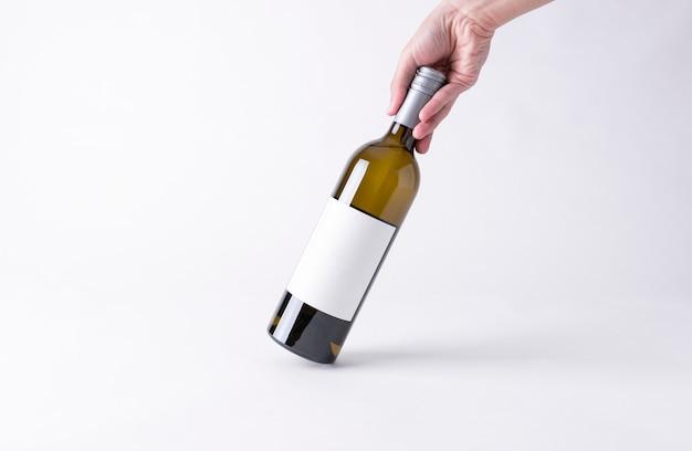 Main tenant une bouteille de vin pour la maquette. étiquette vierge sur un fond gris. Photo Premium
