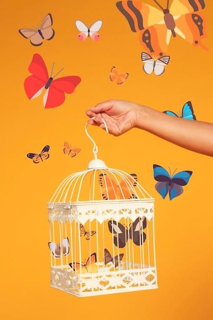 Main tenant une cage à oiseaux avec des papillons iconos Photo gratuit