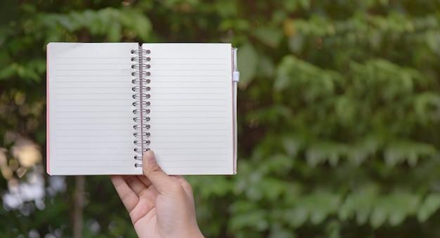 Main tenant un cahier dans l'herbe Photo Premium