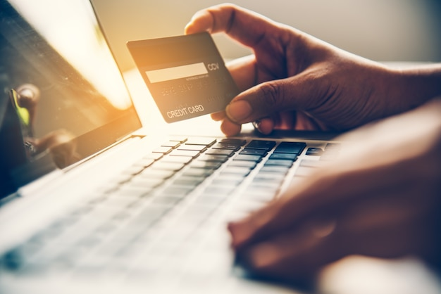 Main Tenant Une Carte De Crédit Dans Leurs Mains Et Trouver Des Informations Sur Un Produit à L'aide De Leur Appareil Mobile Photo Premium