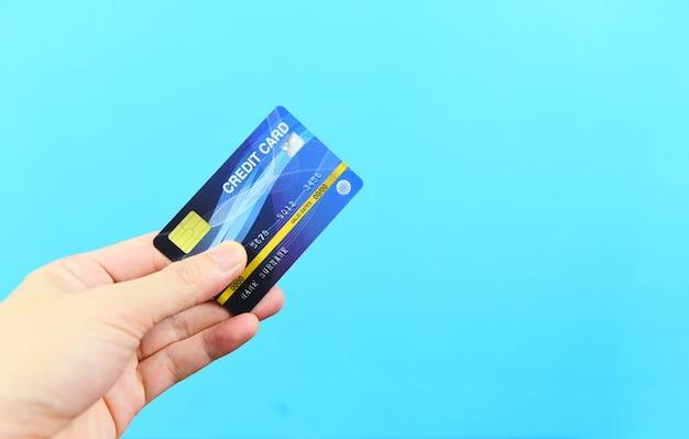 Main Tenant La Carte De Crédit Sur Fond Bleu - Paiement Achats En Ligne Payer Avec La Technologie De Carte De Crédit E Concept De Portefeuille Photo Premium