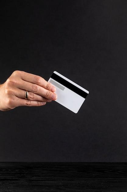 Main tenant une carte de crédit sur fond noir Photo gratuit