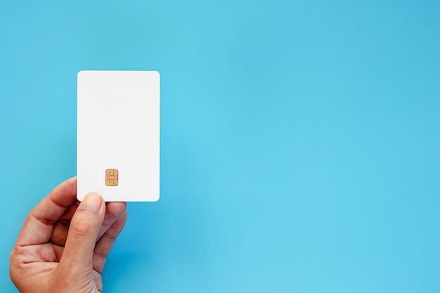 Main tenant une carte à puce vierge sur fond bleu Photo Premium