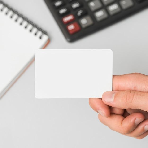 Main tenant une carte de visite dans un environnement de bureau Photo gratuit