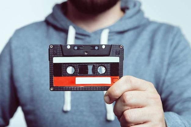 Main tenant une cassette. cassette utilisée. cassette audio. Photo Premium