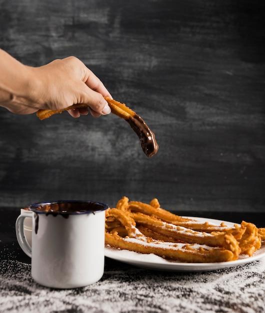 Main tenant un churros au chocolat et une tasse Photo gratuit