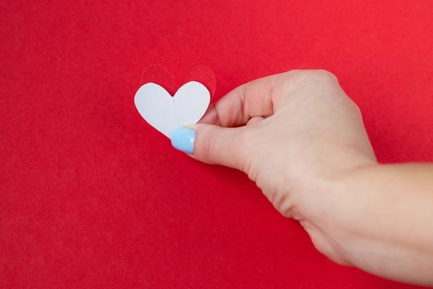 Main tenant un coeur blanc sur fond rouge. fond pour la saint valentin Photo Premium