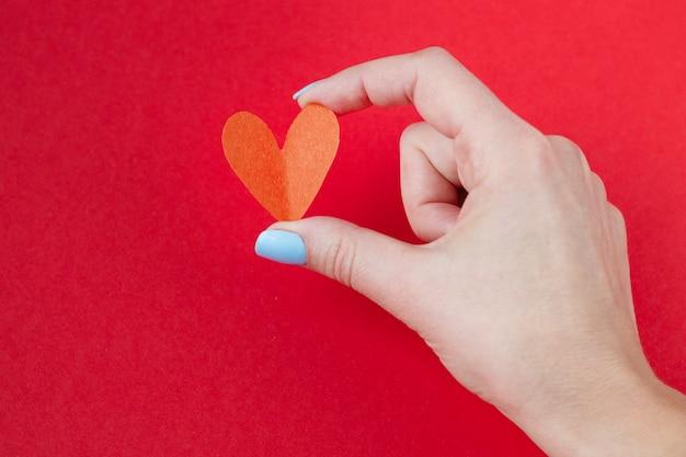 Main tenant un coeur rouge sur fond rouge. fond pour la saint valentin Photo Premium