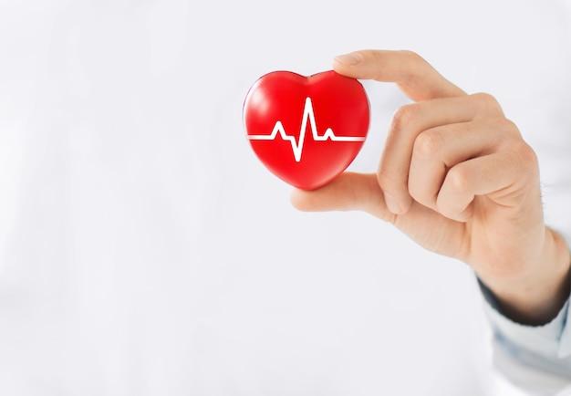 Une main tenant un coeur rouge avec la ligne ecg. Photo Premium