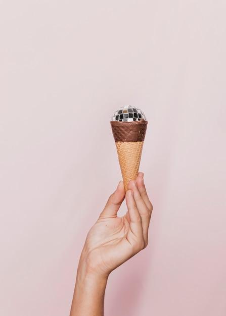 Main tenant un cornet de crème glacée Photo gratuit