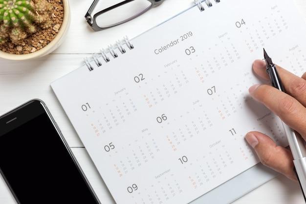 Main tenant un crayon sur le calendrier avec smartphone et lunettes Photo Premium