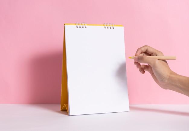 Main tenant un crayon pour l'écriture de marquage sur le calendrier en spirale de papier maquette sur fond rose. Photo Premium