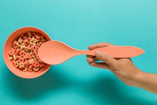 Main tenant la cuillère près de la coupe avec les lettres de l'alphabet comestible Photo gratuit