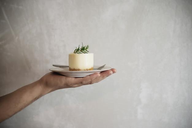 Main tenant un dessert sur fond de mur de ciment plateau Photo gratuit