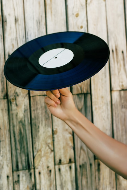 Main tenant un disque vinyle sur fond en bois Photo Premium
