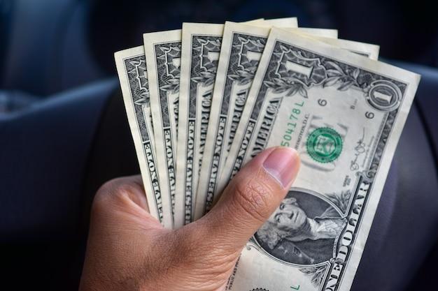 Main tenant un dollar en voiture Photo Premium