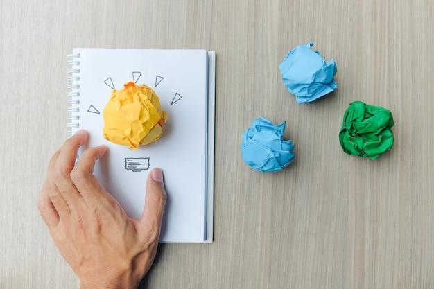 Main Tenant Du Papier Froissé Coloré Sur Une Table En Bois. Photo Premium