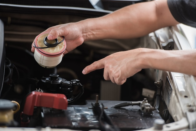 Main tenant le filtre à essence et pointant vers le moteur automobile Photo Premium