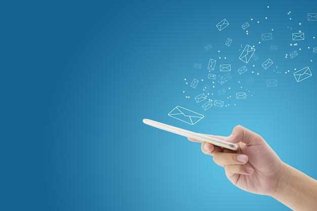 Main tenant l'homme vérifier et envoyer un message avec email dans un téléphone sur fond bleu. Photo Premium