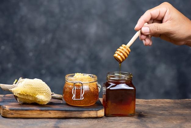 Main tenant une louche de miel en bois Photo Premium