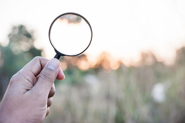 Main tenant la loupe à la recherche Photo Premium