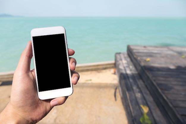 Main tenant la maquette de téléphone intelligent Photo Premium