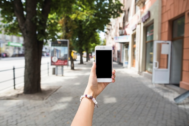 Main tenant mobile avec écran blanc à la rue Photo gratuit