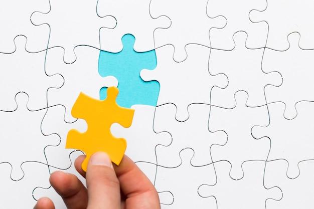 Main tenant un morceau de puzzle jaune pour compléter la mission Photo gratuit