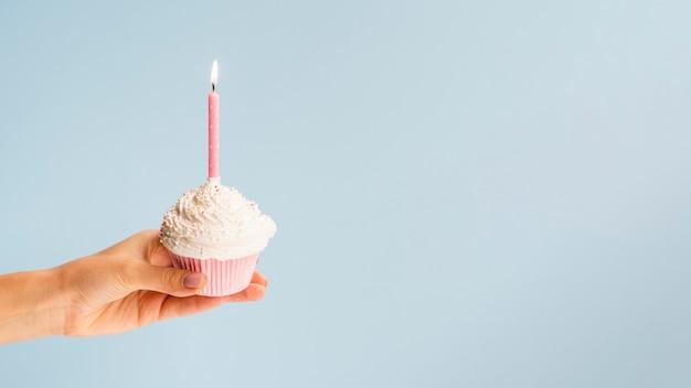 Main tenant un muffin d'anniversaire sur fond bleu Photo gratuit