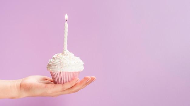 Main tenant un muffin d'anniversaire sur fond rose Photo gratuit