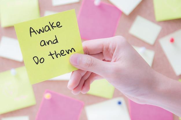 Main tenant un papier à lettres ou l'afficher avec des mots / réveillez-vous et faites-les. concept de motivation Photo Premium