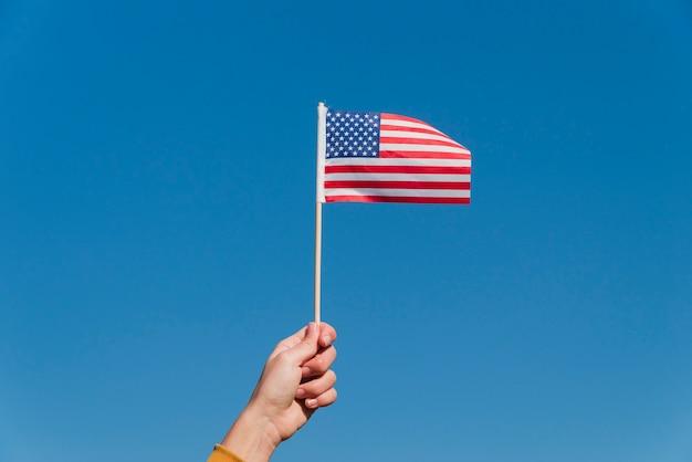 Main tenant un petit drapeau américain Photo gratuit