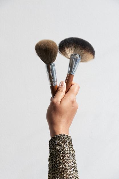 Main tenant des pinceaux de maquillage Photo gratuit