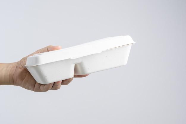 Main tenant des plats thaïlandais dans une boîte à nourriture en papier en fibres végétales Photo Premium