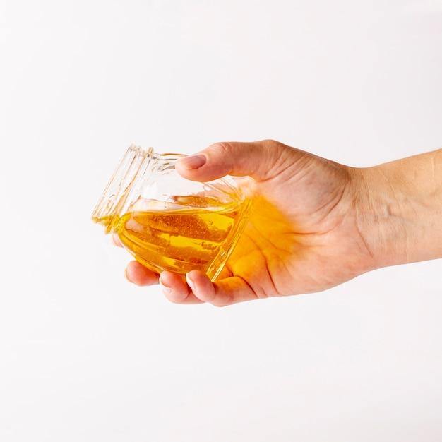 Main tenant un pot avec du miel Photo gratuit