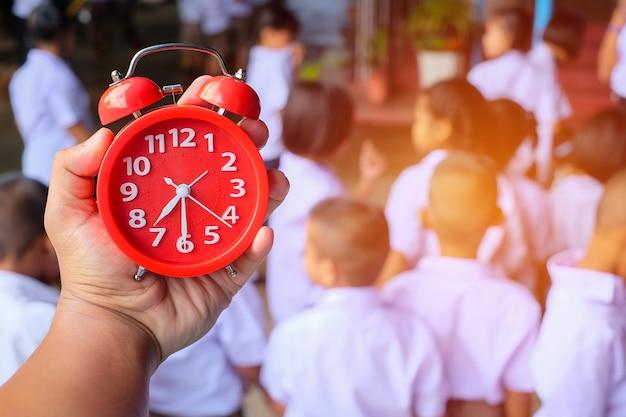 Une Main Tenant Un Réveil Rouge Sur L'image Floue Du Groupe D'étudiants Et Plan De Travail à L'école En Thaïlande. Le Travail D'équipe Doit Correspondre. Allez à L'école, Gros Plan Et Flou. Photo Premium