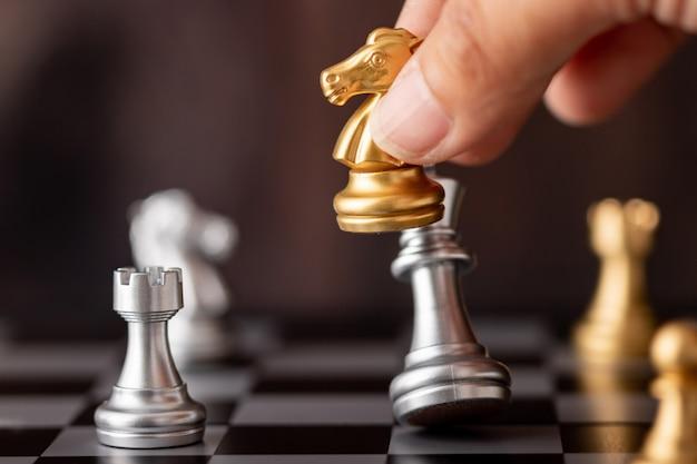 Main tenant le roi d'argent d'attaque de cheval d'or dans le jeu Photo Premium